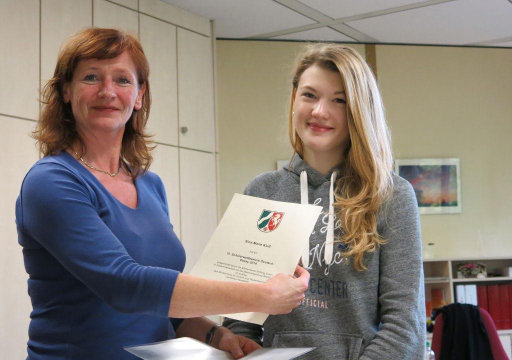 Sina-Marie Kluß erhält die Urkunde für die erfolgreiche Teilnahme am Essay-Wettbewerb